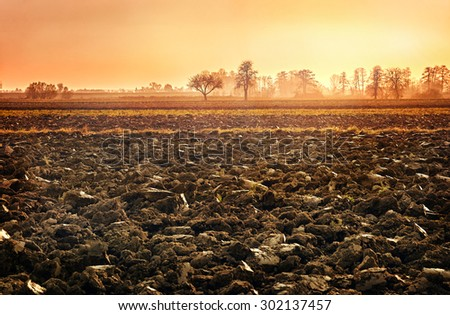 plowed soil. spring field. sunset over ploughed field. Countryside landscape