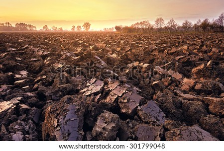 plowed soil. spring field. sunset over ploughed field. Countryside lanscape - stock photo