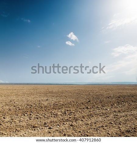 plowed spring agriculture field under sun in clouds - stock photo