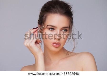 Plucking eyebrows - stock photo