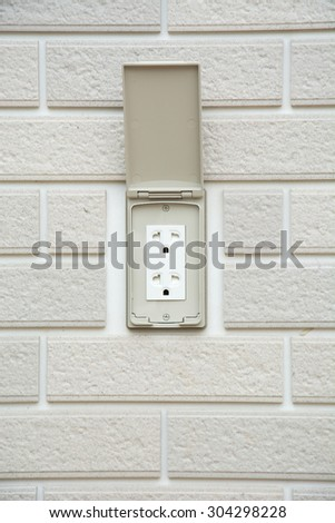plug on grey brick wall