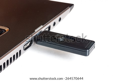 Plugging removable flash disk memory into laptop USB slot - stock photo