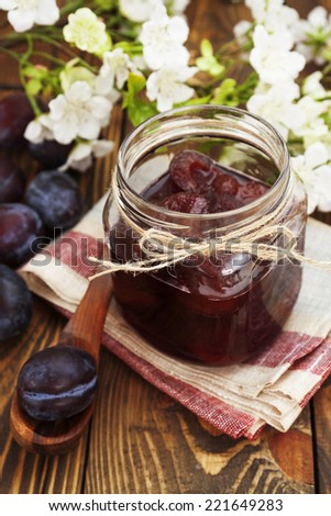 Plum jam in a glass jar on the wooden table