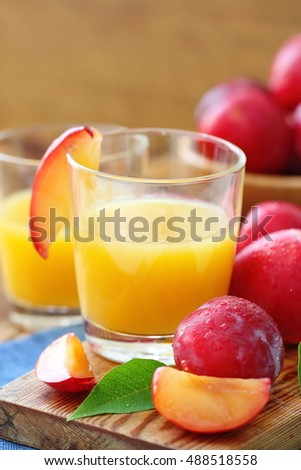Plum juice and ripe fresh fruit on the table