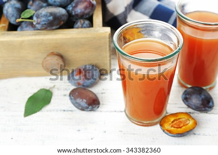 Plum Juice in glasses with fresh fruits - stock photo