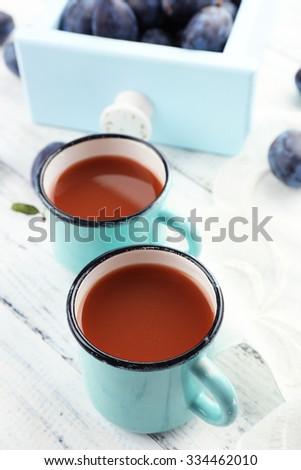 Plum Juice in mugs with fresh fruits - stock photo