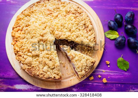 plum tart with  crumbleon rustic purple background - stock photo