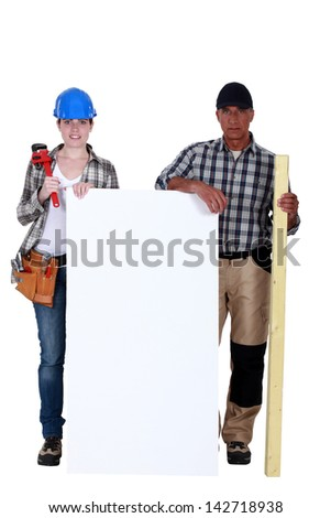 Plumber and carpenter stood by blank poster - stock photo