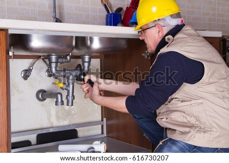 plumber at work to fix a sink