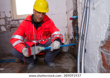 plumber at work with pipes
