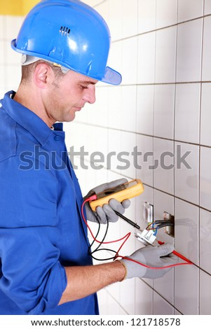 Plumber checking wiring with a voltmeter - stock photo