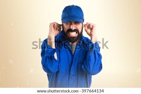 Plumber covering his ears over ocher background - stock photo