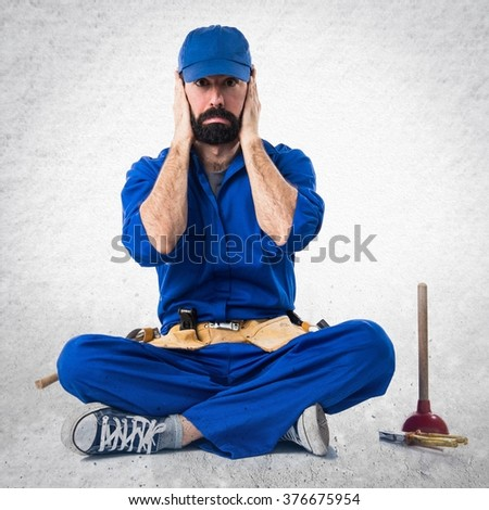 Plumber covering his ears over textured background - stock photo