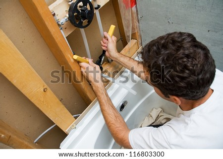 Plumber cutting in the hot and cold water lines for a shower/tub combo. - stock photo