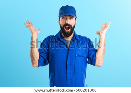 Plumber doing surprise gesture over colorful backgound