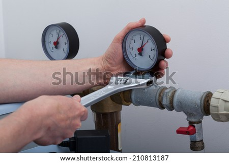 Plumber during work with a wrench, horizontal
