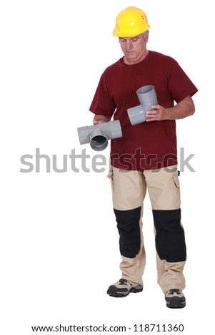 Plumber fitting two plastic pipes together - stock photo