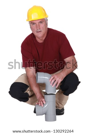 plumber fixing a plastic pipe - stock photo
