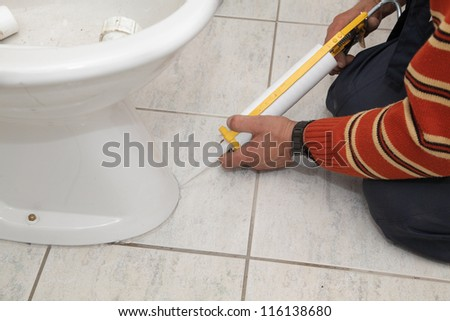 Plumber fixing bidet in a washroom with  silicone cartridge - stock photo