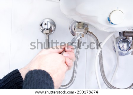 plumber fixing electric water heater - stock photo