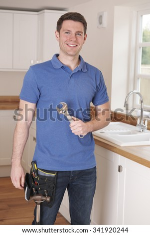 Plumber Fixing Kitchen Tap With Adjustable Wrench - stock photo