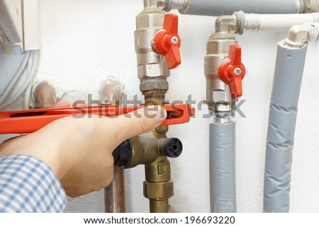 plumber fixing pipe system - stock photo