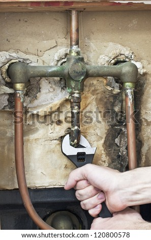 Plumber fixing the leaking water pipe - stock photo