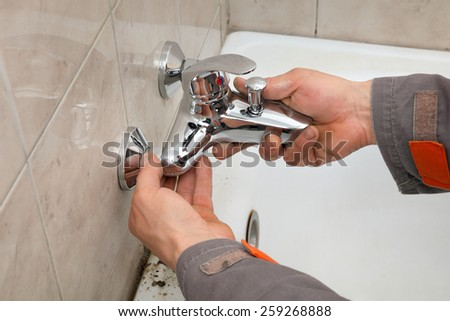 Plumber hands fixing water  tap in a bathroom - stock photo