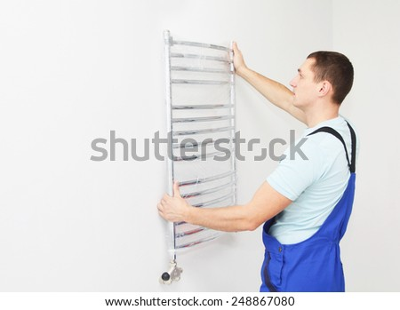 Plumber hanging towel rail - stock photo