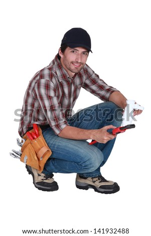 plumber holding a plastic pipe and a spanner - stock photo