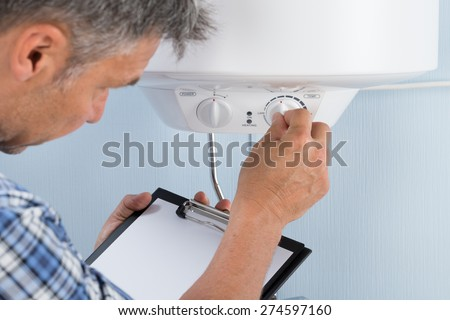 Plumber Holding Clipboard Adjusting Temperature Of Electric Boiler - stock photo