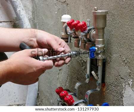 Plumber installing pipes in home - stock photo