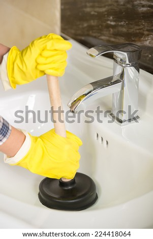 Plumber is cleaning sink with plunger. - stock photo