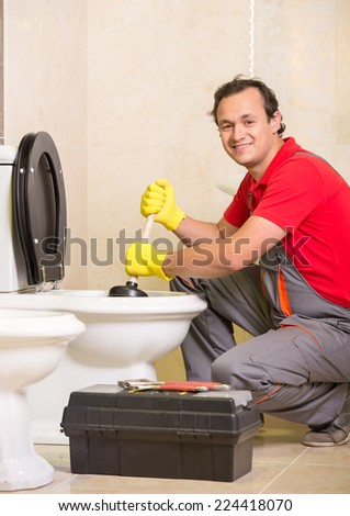 Plumber is cleaning sink with plunger in the bathroom.