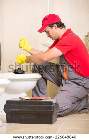 Plumber is cleaning sink with plunger in the bathroom. - stock photo