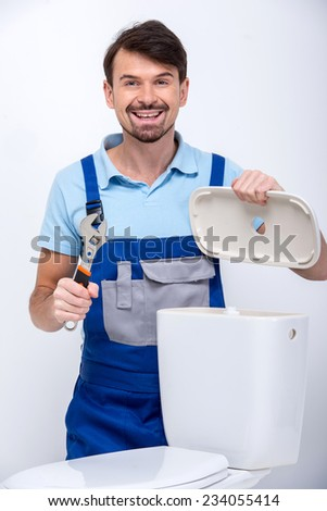 Plumber is repairing a flush toilet, on white background. - stock photo