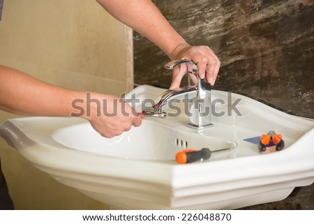 Plumber is repairing an hot-water heater in bathroom. - stock photo