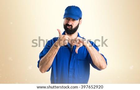 Plumber making good-bad sign over ocher background - stock photo