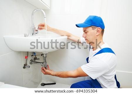plumber man repair leaky faucet tap