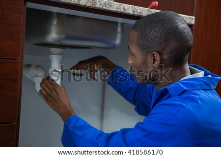 Plumber repairing a sink in kitchen