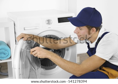 Plumber repairing washing machine