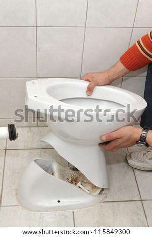 Plumber replacing broken toilet in a washroom - stock photo
