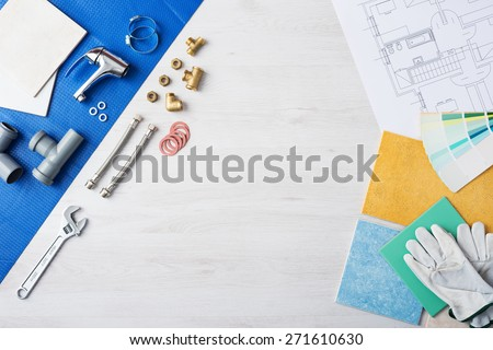 Plumber's work table banner with work tools, faucet, tiles and color swatches, top view, copy space at center - stock photo