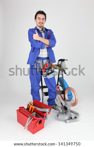 Plumber standing with various tools and material - stock photo