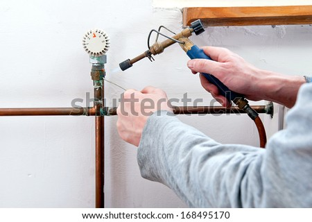 Plumber using welding gas torch to solder copper central heating pipes. - stock photo