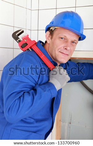 Plumber with a large red wrench held over his shoulder