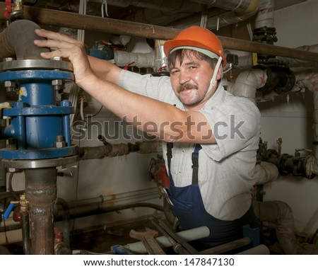Plumber with pipe wrench works