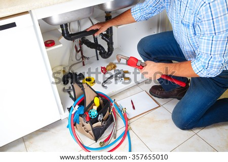 Plumber with Plumbing tools on the kitchen. Renovation. - stock photo