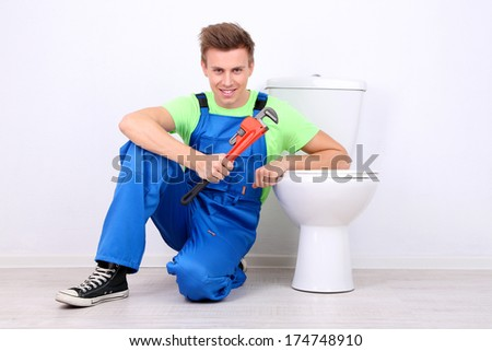 Plumber with toilet plunger on light background - stock photo