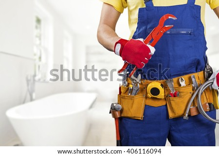 plumber with tool belt standing in bathroom - stock photo
